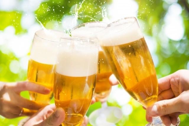 乾杯している写真。ビールグラス4つに並々とビールが注がれていて泡がはじけている。